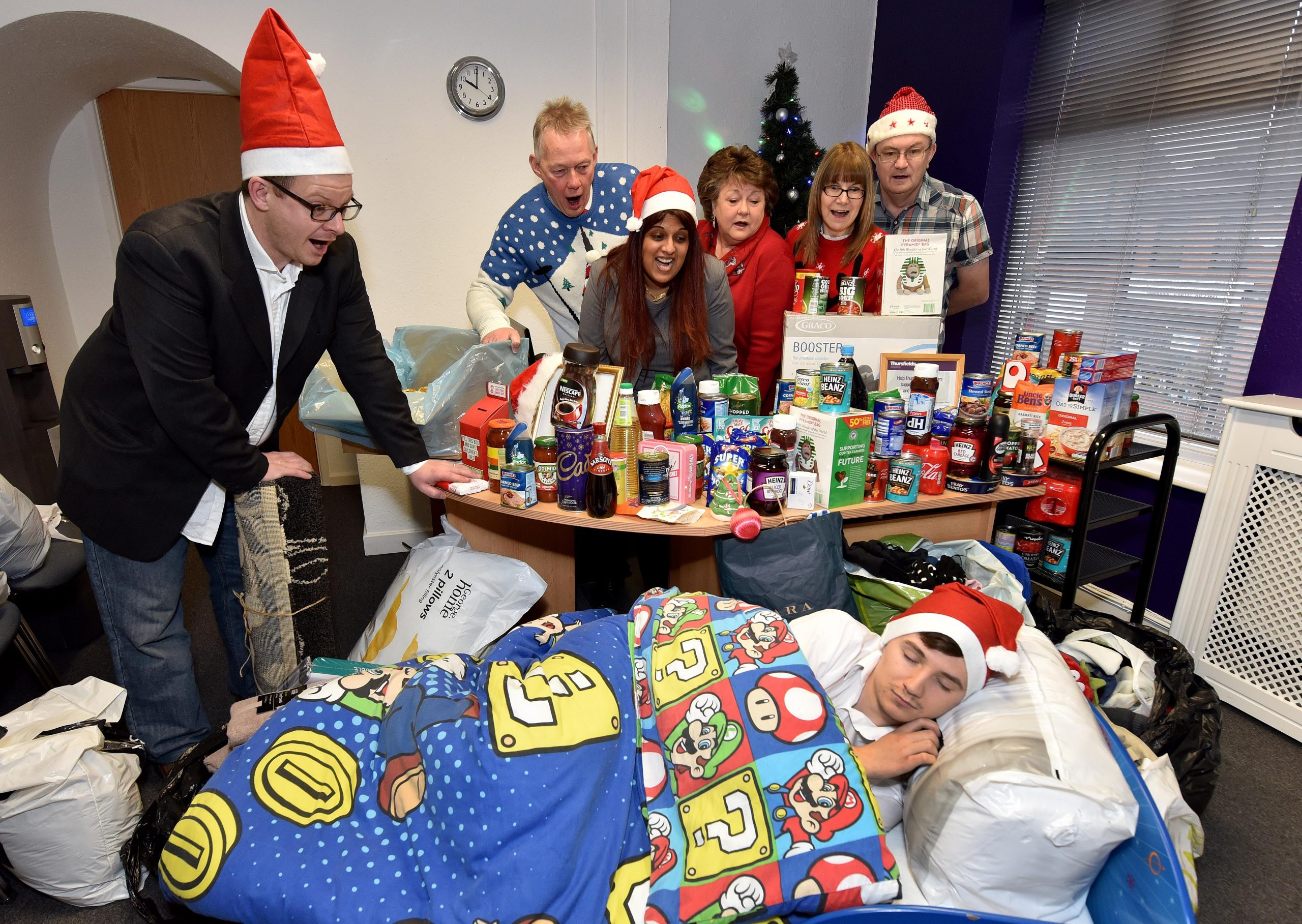 DUDLEY COPYRIGHT EXPRESS&STAR TIM THURSFIELD 23/12/16 Property lawyers Thursfields, Dudley Street, Sedgley, with some of the items donated to them for charity Hope Into Action Black Country, which even included a child sized bed! Pictured are Matt Lambert from the charity, Kevin Drew, Deepa Patel, Lorraine Fellows, Tracey Side, Paul Brindley, and sleeping is Ryan Harding from Thursfields