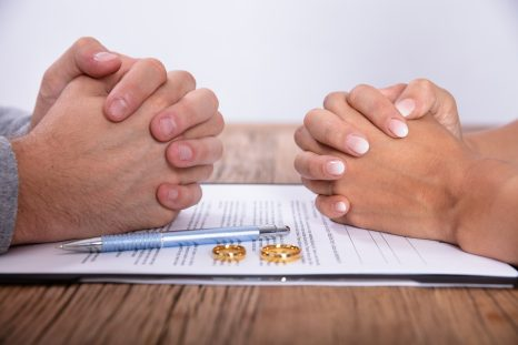 Couple's Hand With Divorce Agreement And Golden Wedding Rings On Wooden Desk