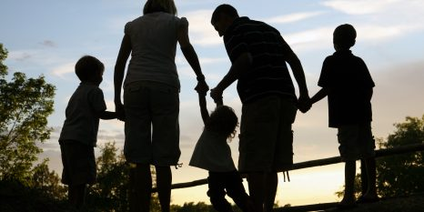 silhouette of young family outdoors holding hands