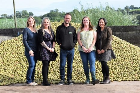 Thursfields team standing by a mound of apples