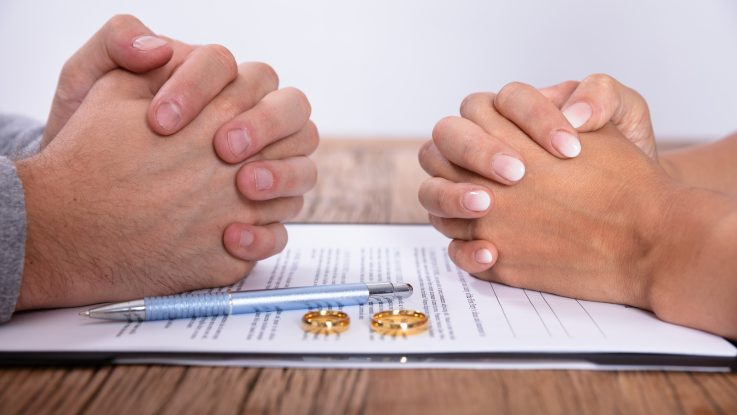 Couples hands with divorce agreement on the table