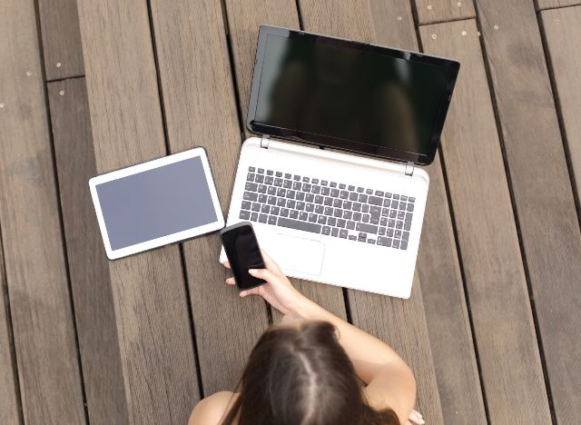 Lady at a table on her mobile phone, with a tablet and laptop